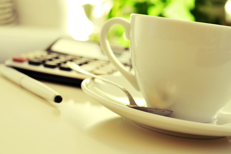 detail of a desk with a calculator and a cup of coffee or tea in an office with a nice atmosphere